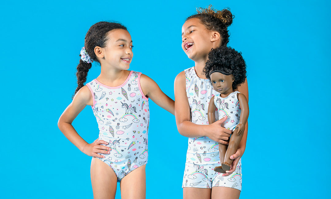Two young girls wearing the Funtastic leotard and unitard, and holding a doll wearing a matching leotard on a solid sky blue background.