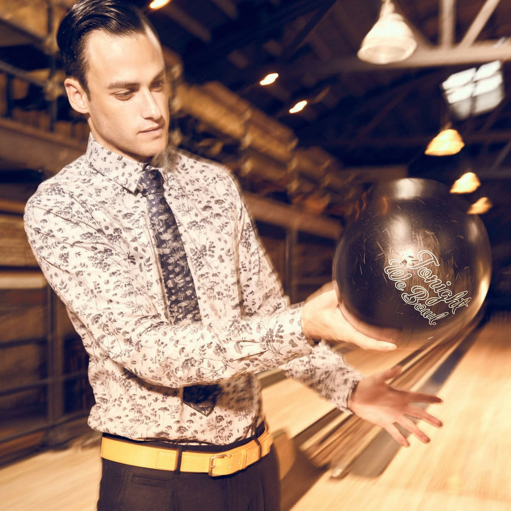 Moods of Norway premium menswear campaign shot, showing a young attractive male model, wearing a shirt and holding a bowling bowl.