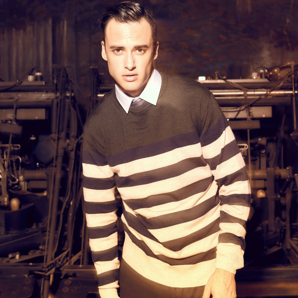 Moods of Norway premium menswear campaign shot, showing  a young attractive male model posing in a stripe sweater.