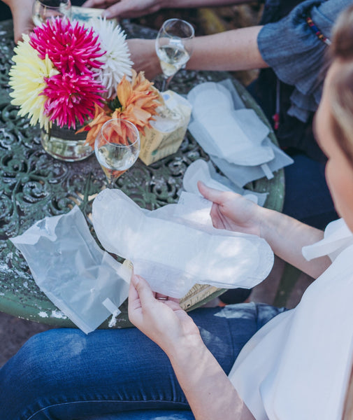 Women sitting at a table with pretty flowers on it holding an open pad and discussing what they see and feel.
