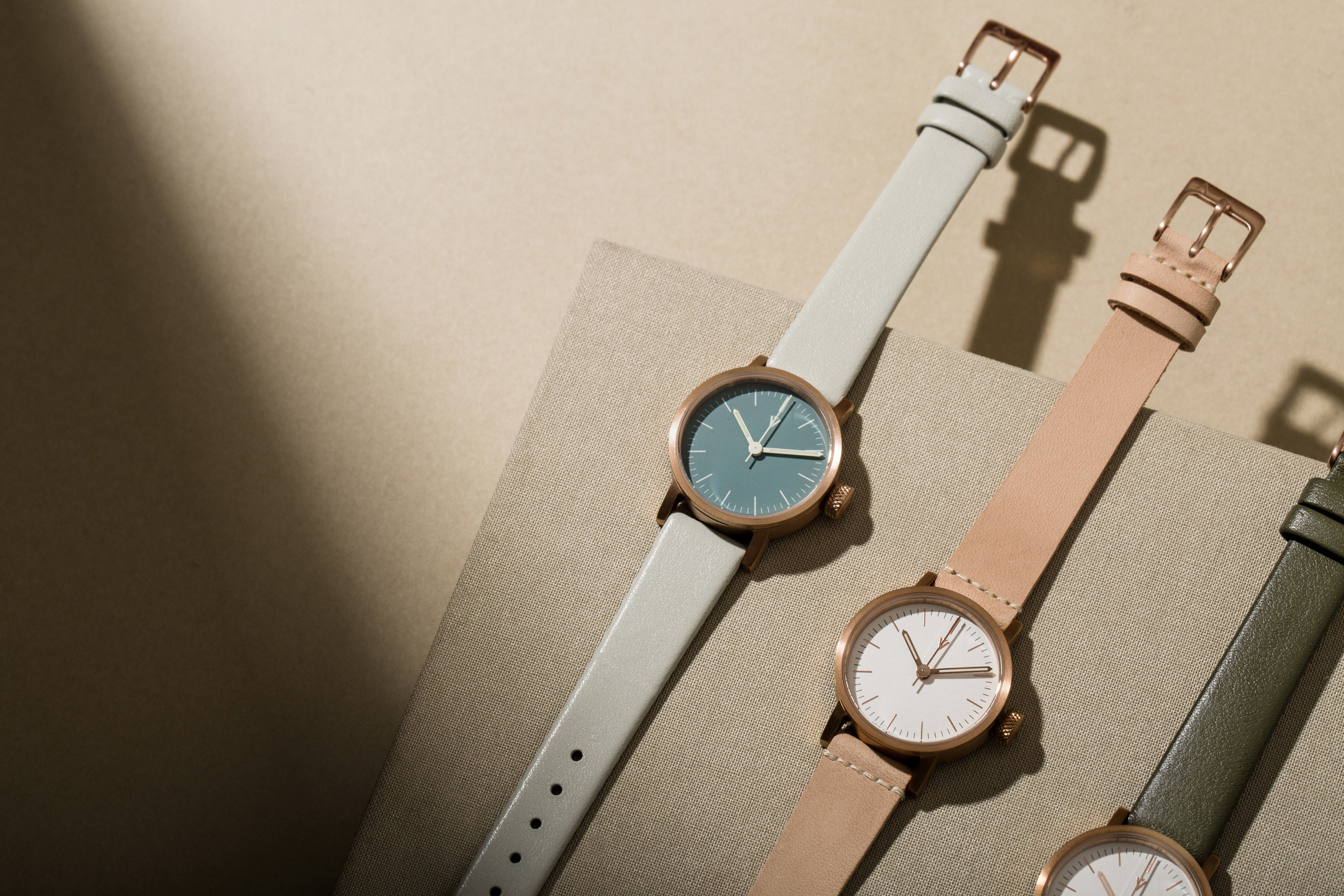 Three copper V03P watches lay on top of a linen book in a neutral toned environment.