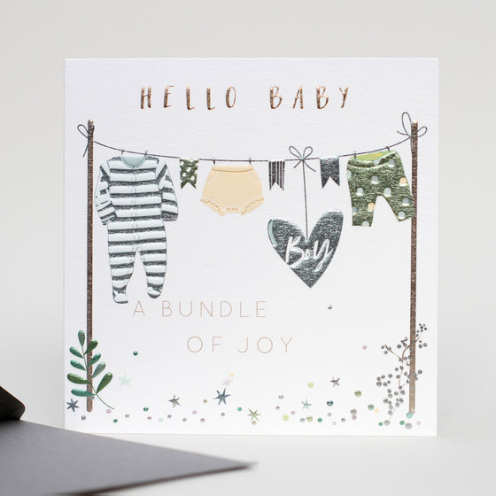 Hello baby, a bundle of joy. Washing line with baby clothes and a blue balloon with boy written on it .