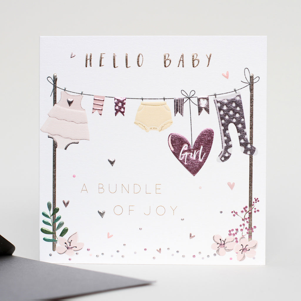 Hand illustrated card with a washing line of baby clothes with a pink heart with Girl written on. Hello Baby, a bundle of joy.