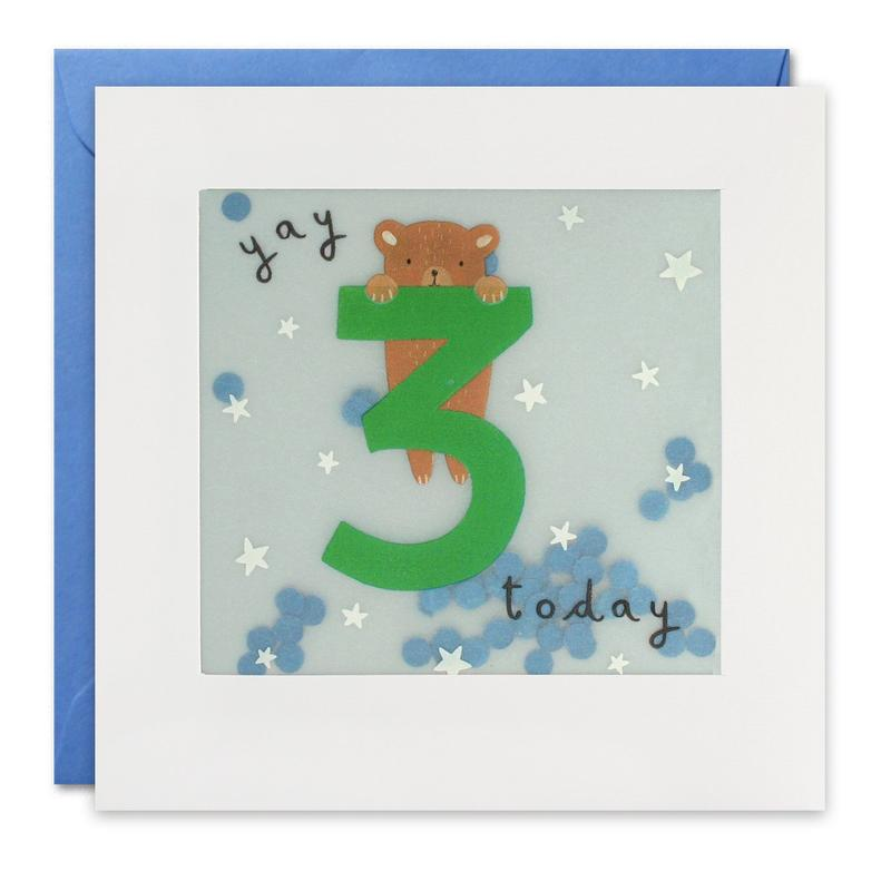 a teddy bear perched on a bright green number 3 with paper confetti and white stars