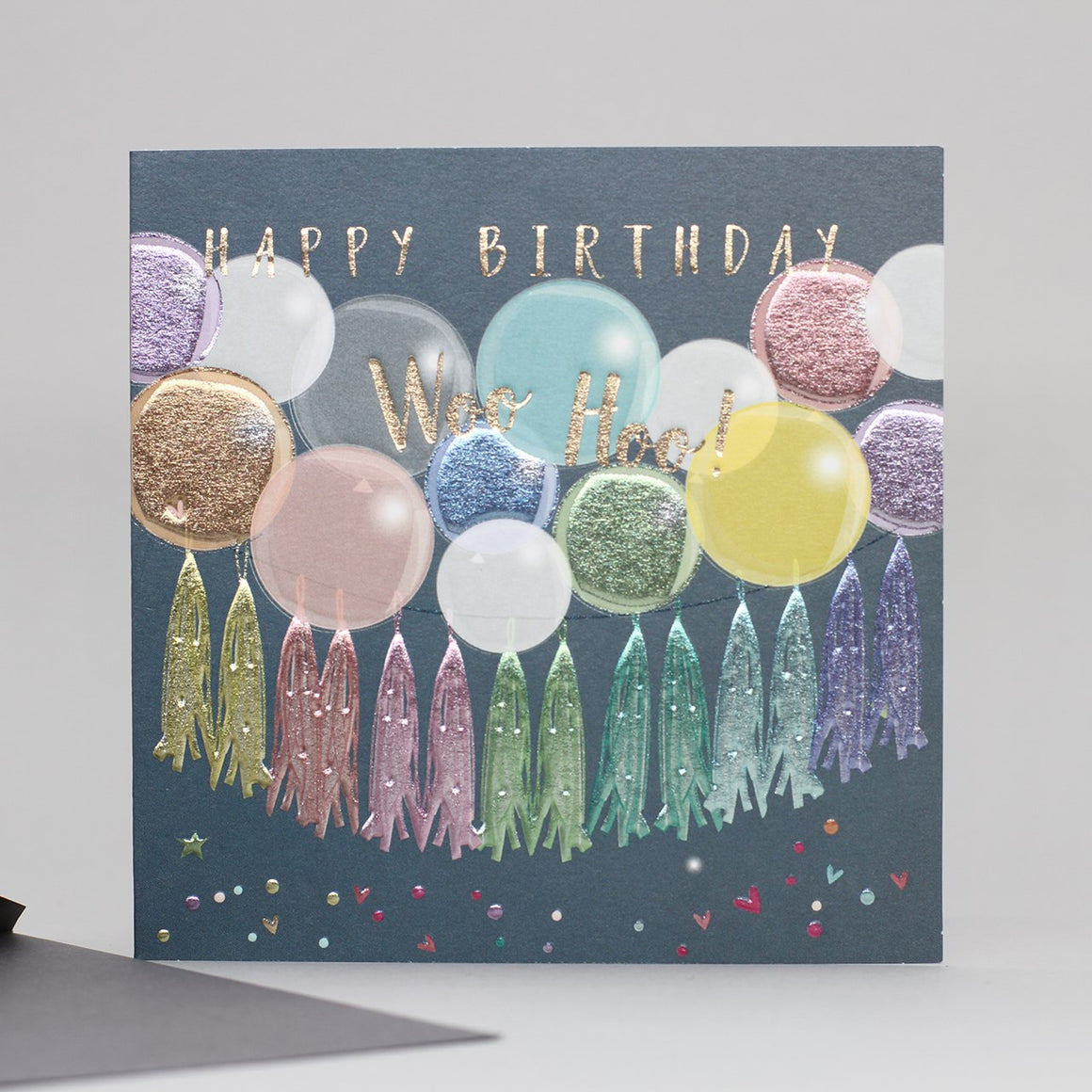 grey card with pastel multi coloured foil finish balloons and tassels happy birthday woo hoo