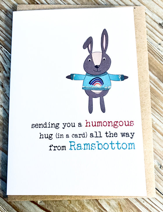 bunny in a blue sweater with a rainbow on with arms stretched out - words say sending you a humongous hug (in a card) all the way from Ramsbottom
