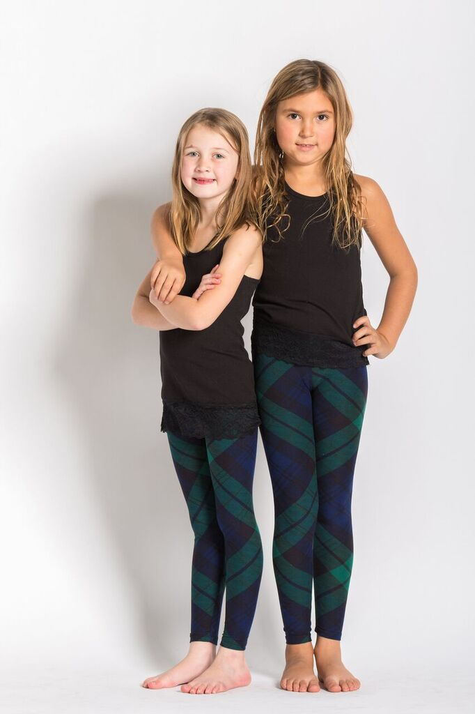 front view kids watch tartan leggings. this dark green and navy blue plaid with hints of black can be worn casually or dressy! Plaid design is angled for a more visually pleasing look - also helps with pattern symmetry and matching at seams.