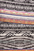 close up view long maxi skirt, ankle length, one size; print design that is primarily white with threads of colours and black. Perfect to match with any colour top. Super soft, stretchy, versatile, great for summer and vacations!