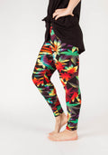 side view of one size adults leggings, pattern features large marijuana leaves in yellow, red, and green with a black background.