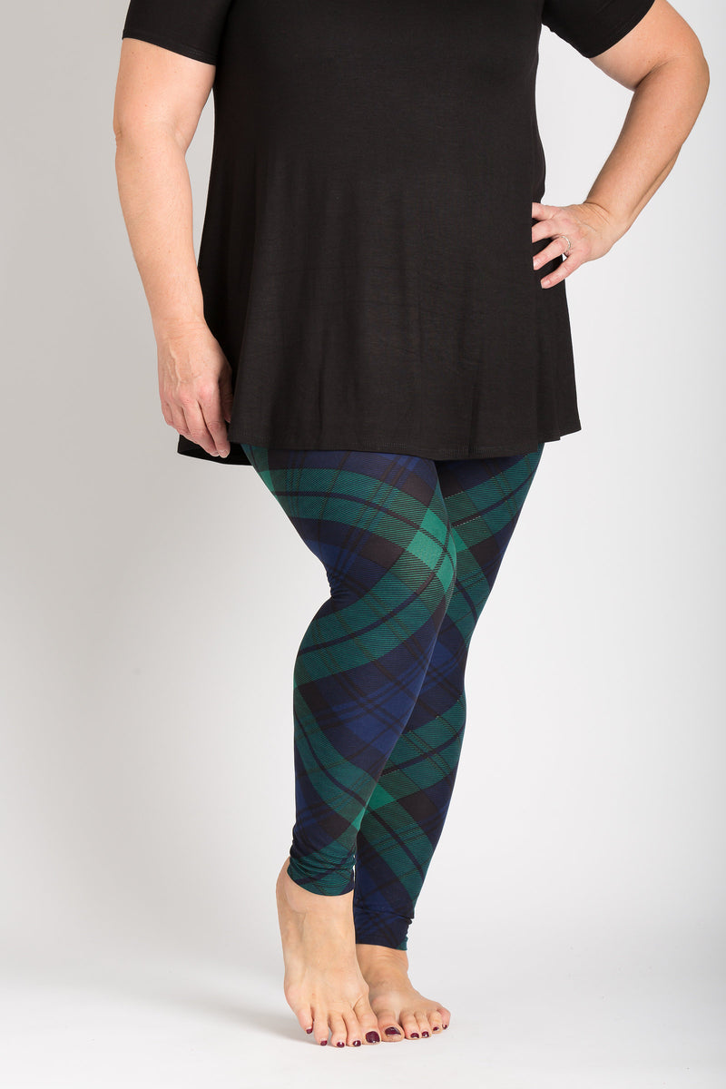 front view adults plus size black watch tartan leggings. this dark green and navy blue plaid with hints of black can be worn casually or dressy! Plaid design is angled for a more visually pleasing look - also helps with pattern symmetry and matching at seams. Fits 2X-5X!