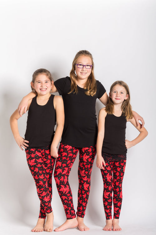 front view kids size Canada theme leggings - black base with red maple leaves - leaves have subtle vein designs in white colour. Perfect for Canada day and travelling! Ultra Canadian!