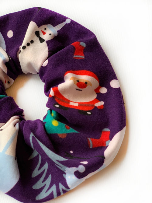 purple/blue scrunchie with christmas design; santa clause, christmas tree, socks, and snowmen