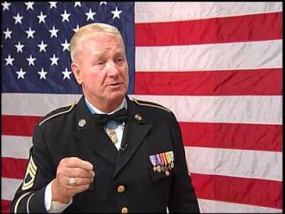 Sammy Davis, medal of honor recipient in front of the american flag at shot show