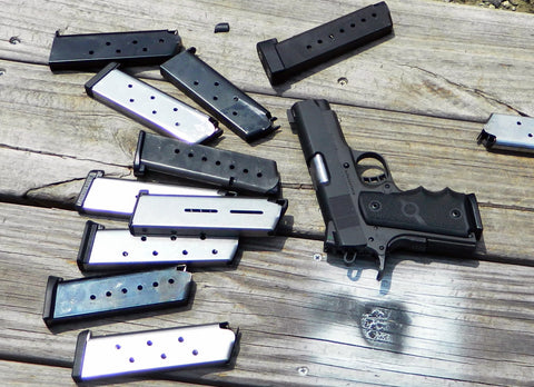 semi automatic 9mm pistol with 10 loose magazines on a wooden table