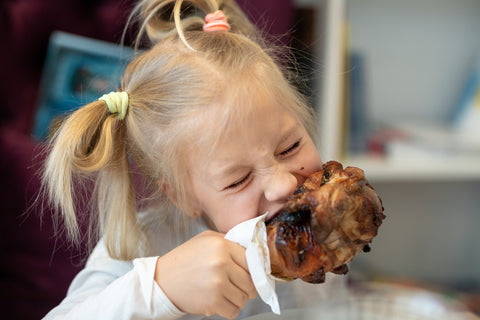 little girl eating grilled chicken