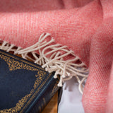 Lambswool throw in coral with white fringe