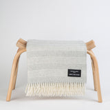 soft white alpaca throw with light grey lines and white fringe