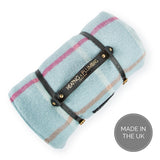 Rolled picnic rug with navy blue carrying leather strap