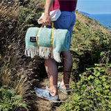 mint green picnic blanket with yellow leather strap