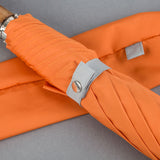 grey tie on an orange folding umbrella