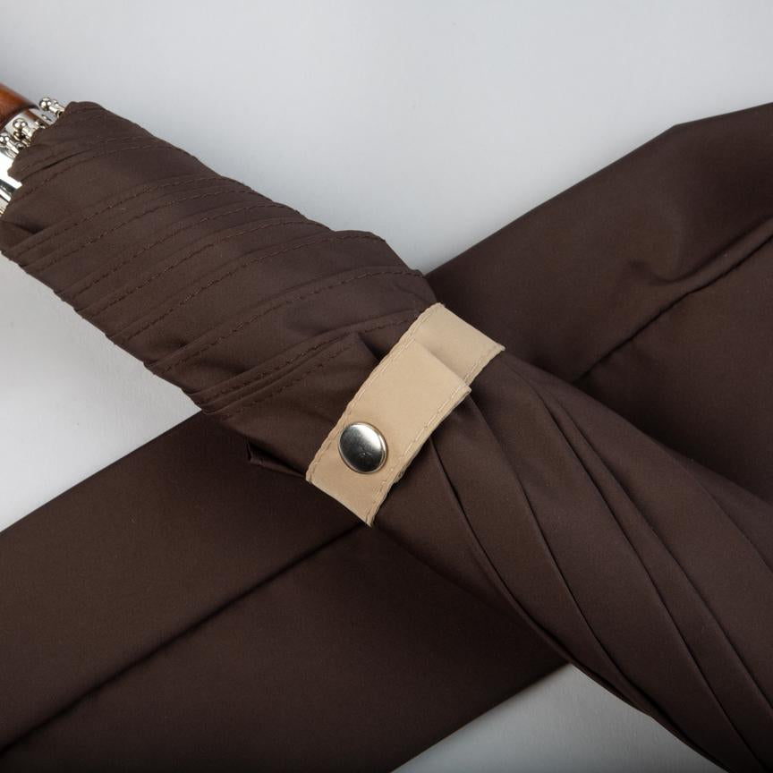 sand coloured tie on dark brown folding umbrella