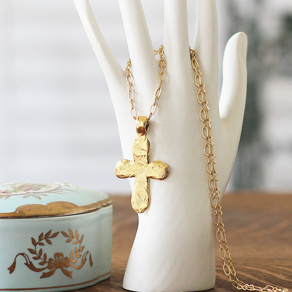 Gold Hammered Cross Pendant Necklace displayed on hand mannequin