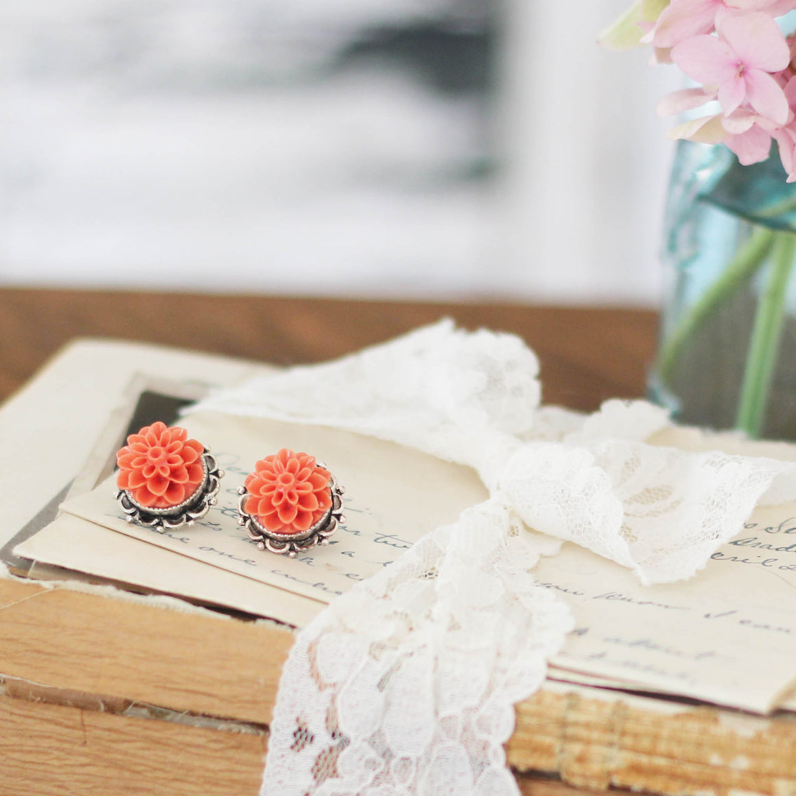 Dahlia Post Earrings Flame Orange on vintage letter and books