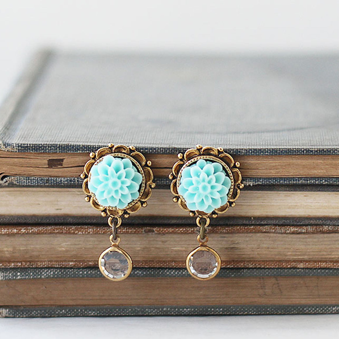 Dahlia Flower Earrings with Crystal Dangle Aqua on book
