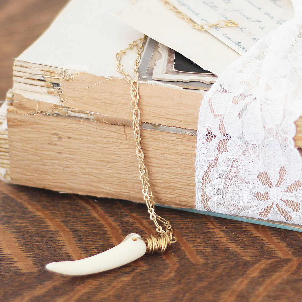 cream Deer Antler Necklace on vintage book