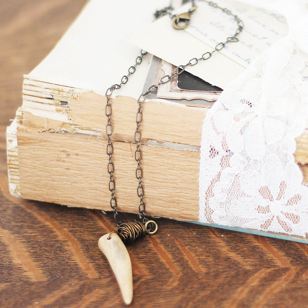cafe au lait Deer Antler Necklace with vintage books on dresser