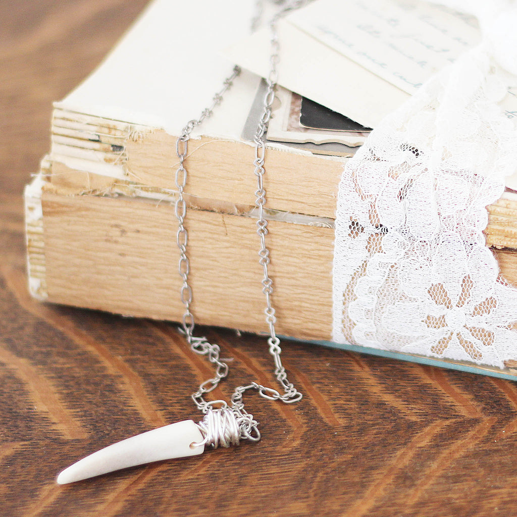 gray Deer Antler Necklace on vintage books