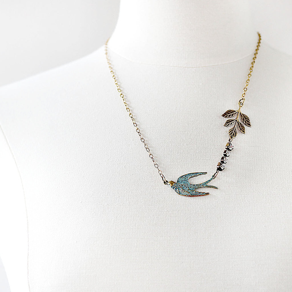 Flying Swallow Bird Necklace Patina Blue and Gold Toned Brass mannequin front