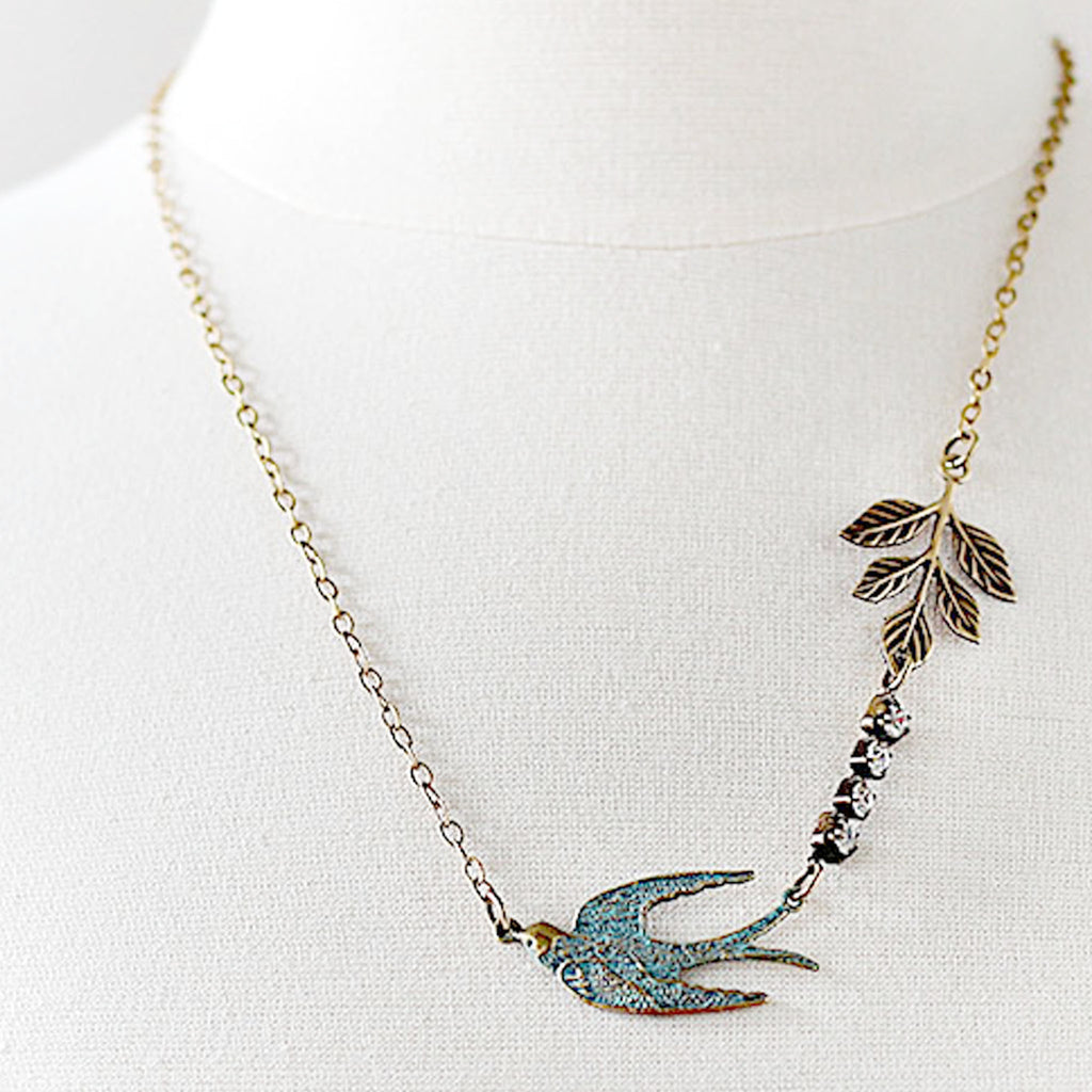 Flying Swallow Bird Necklace Patina Blue and Gold Toned Brass close on mannequin
