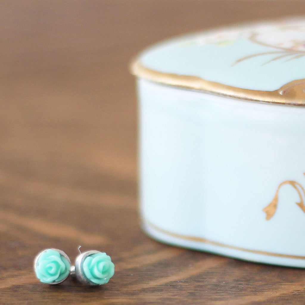 Post Rose Earrings Aqua Green lying on a dresser