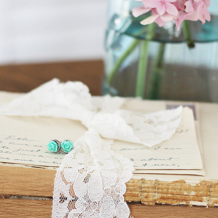 Post Rose Earrings Aqua Green laying on vintage love letter