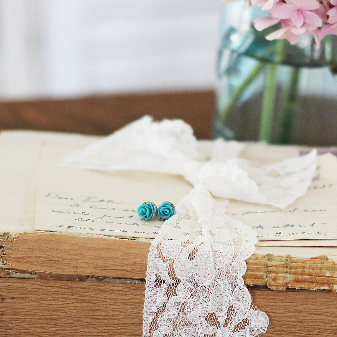 Post Rose Earrings Teal laying on vintage ribbon tied vintage books