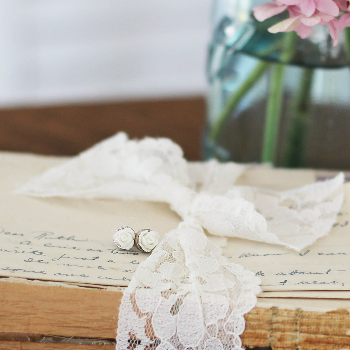 Post Rose Earrings White laying on vintage books