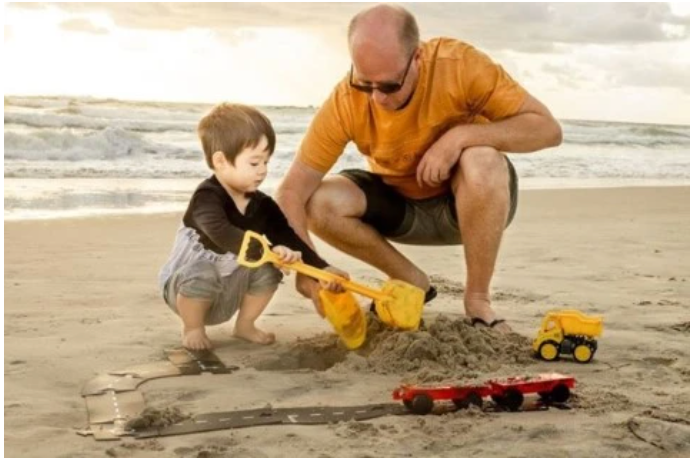 Father and son playing cars on the beach