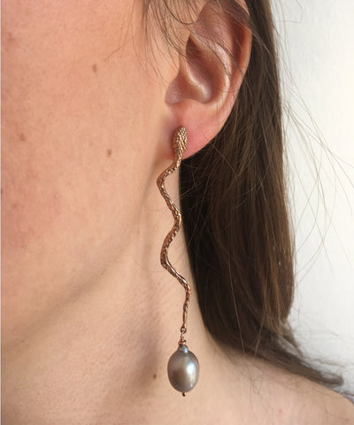 rose gold snake earring with baroque pearl worn