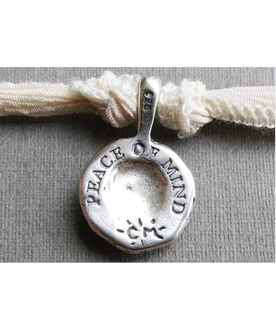 Peace of Mind silver charm bracelet on the back - Catherine Michiels