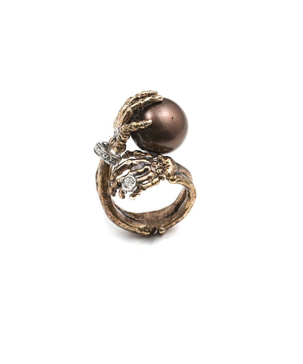 Pearl ring in the hands of a gold and diamond skeleton creator Ring