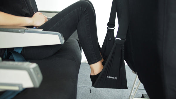 Woman flying with elevated legs in HANGAR Travel Footrest, travel comfort, travel gadget