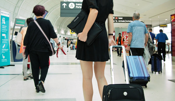 Girl Travelling through airport with luggage