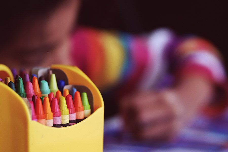Crayons on a blurred background of a child coloring.