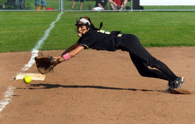 Softball third baseman fielding a ball in play