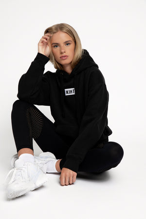 Ethical UK activewear Black slightly oversized drop shoulder unisex hoodie with Kiht logo embroidered patch on the front in contrasting white. Super soft thick fabric with chunky cord detail and hidder inner pockets make this our ultimate hoodie.