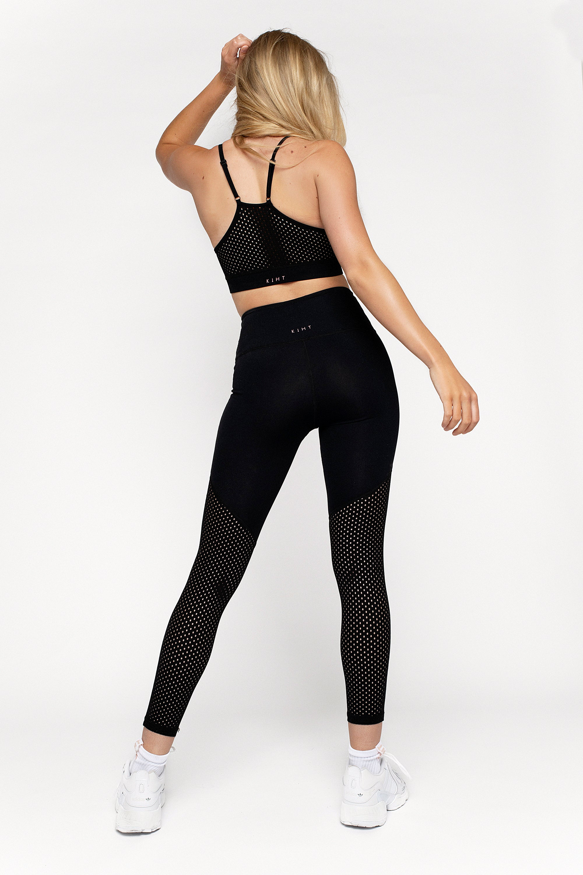 UK Ethical activewear High waisted black gym legging with punched panel back detail on the legs Angled flattering seams on the front and back compressive flattering fit
