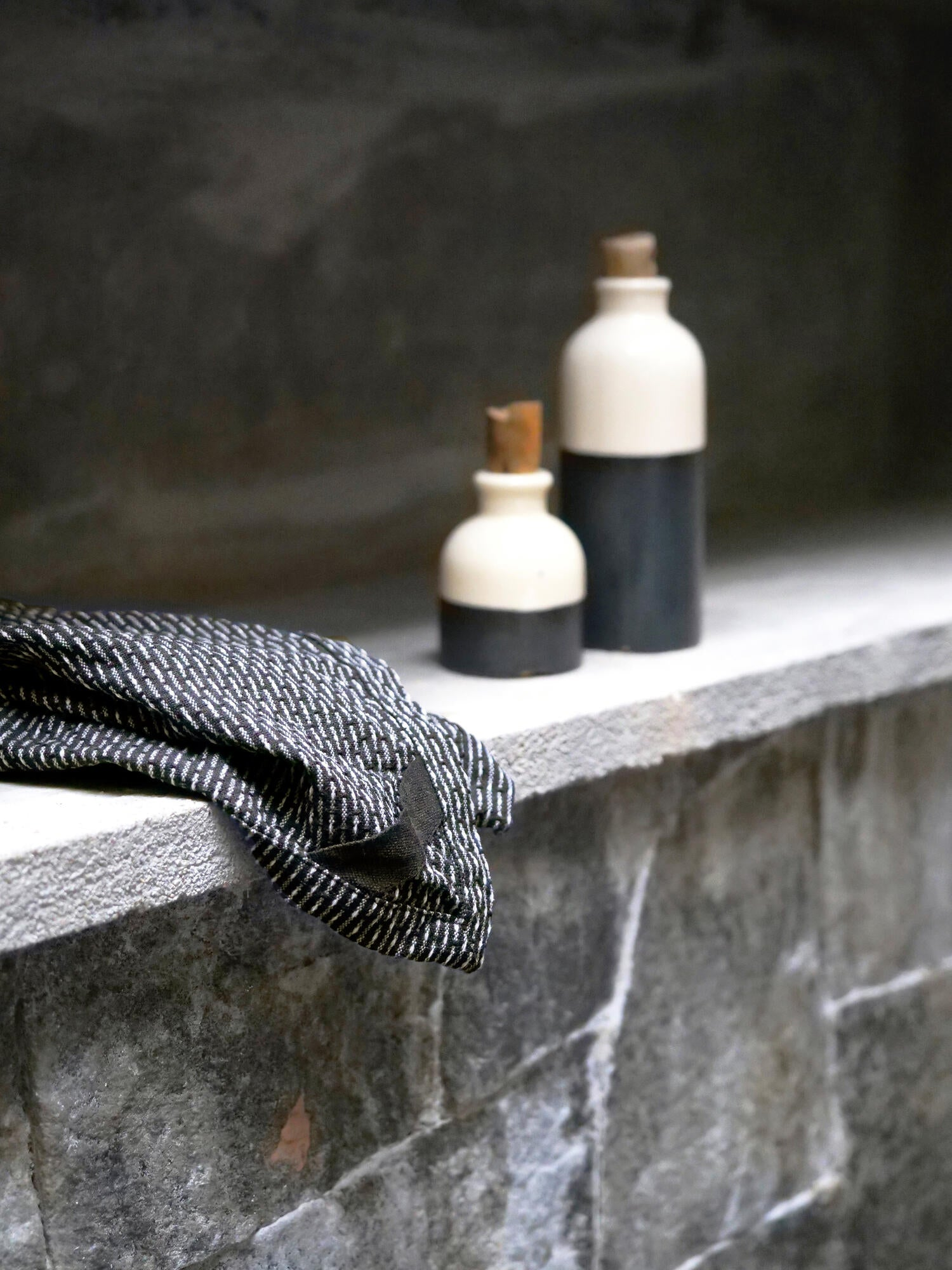 Stone shelf with ceramic bottles and grey cotton wash cloth