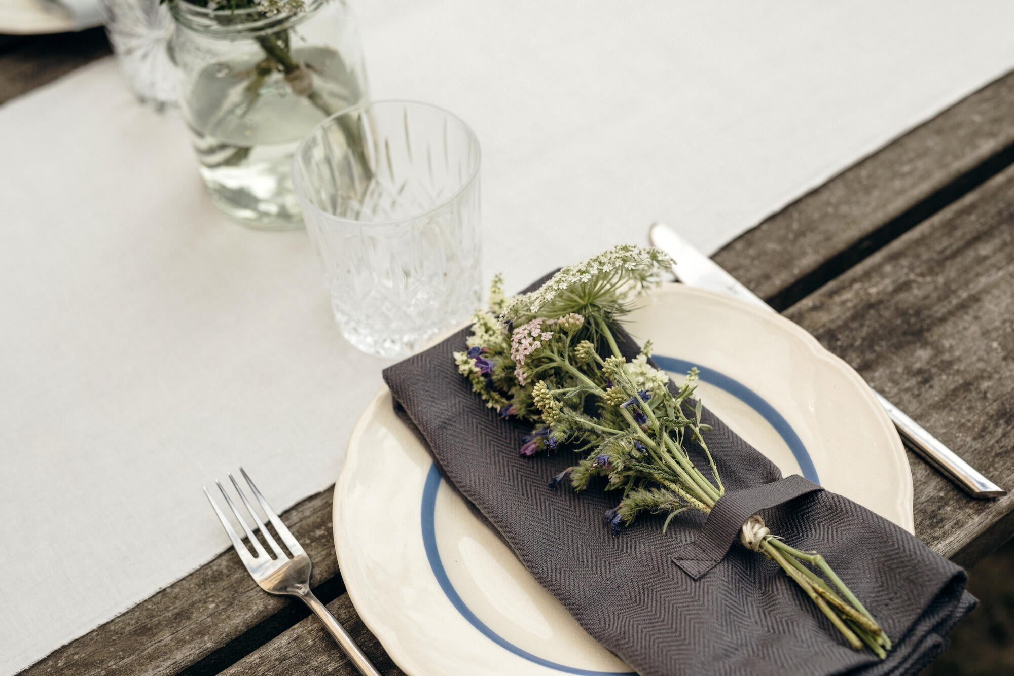 Table laid with grey napkin and flowers, pretty water jug