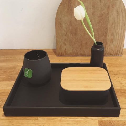 Breakfast tray with mug of tea, butter box and vase of flowers, all black.